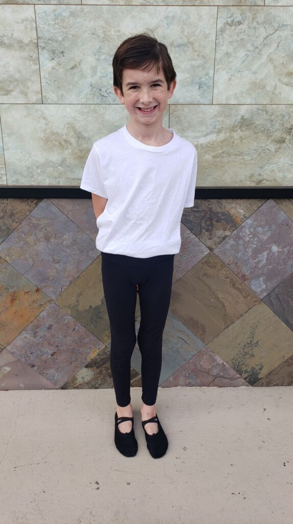 a boy in a white tshirt and black leggings for ballet