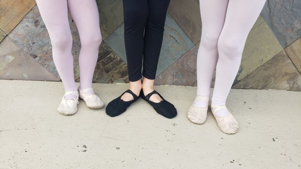 two girls in pink shoes; boy in black ballet shoes