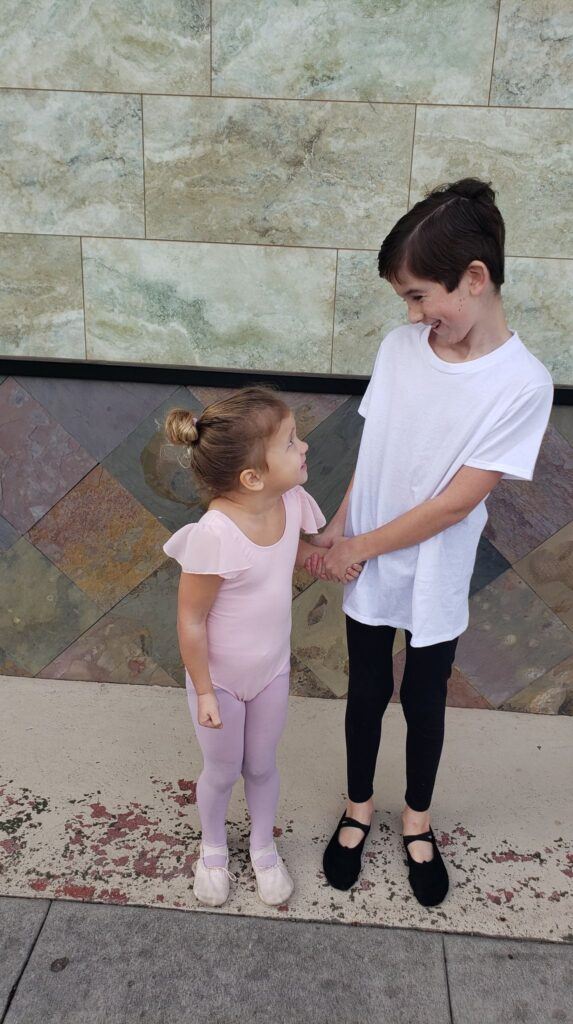 a boy doing ballet with his sister