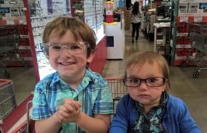 two kids sitting in a costco shopping cart, wearing glasses
