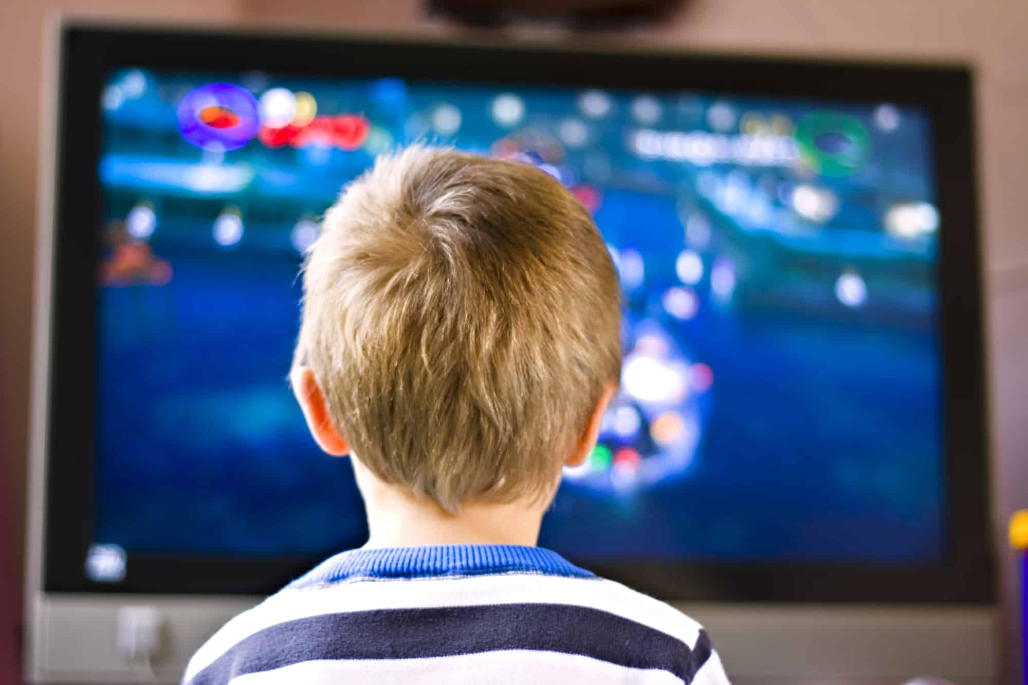 The back of a little boys head in front of an active TV screen.