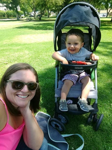 Salty momma Jaymi sitting with her son. Toddler is in a stroller in a Park setting.