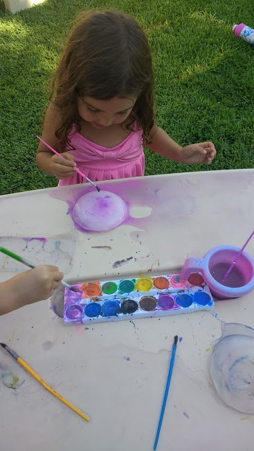 Little girl painting on Ice with water color.