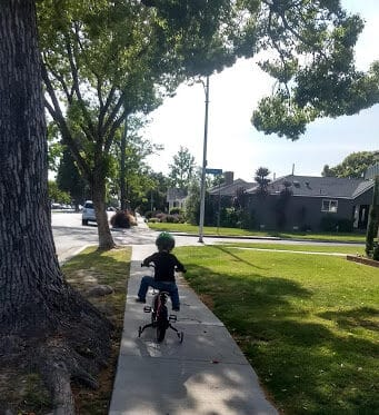Toddler on a bicycle with training wheels outside on the sidewalk.
