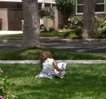 Young girl sitting in her front yard writing in a Notebook.