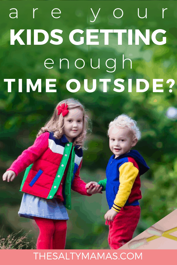 Two children holding hands facing towards the camera by trees. Text overlay: Are your kids getting enough time outside?