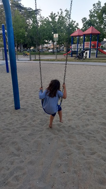 Little girl on a swing set at a park in a play area.
