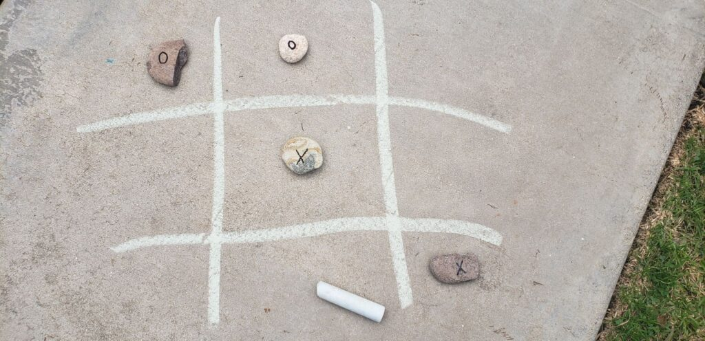 rocks with x and os written on them; tic tac toe lines