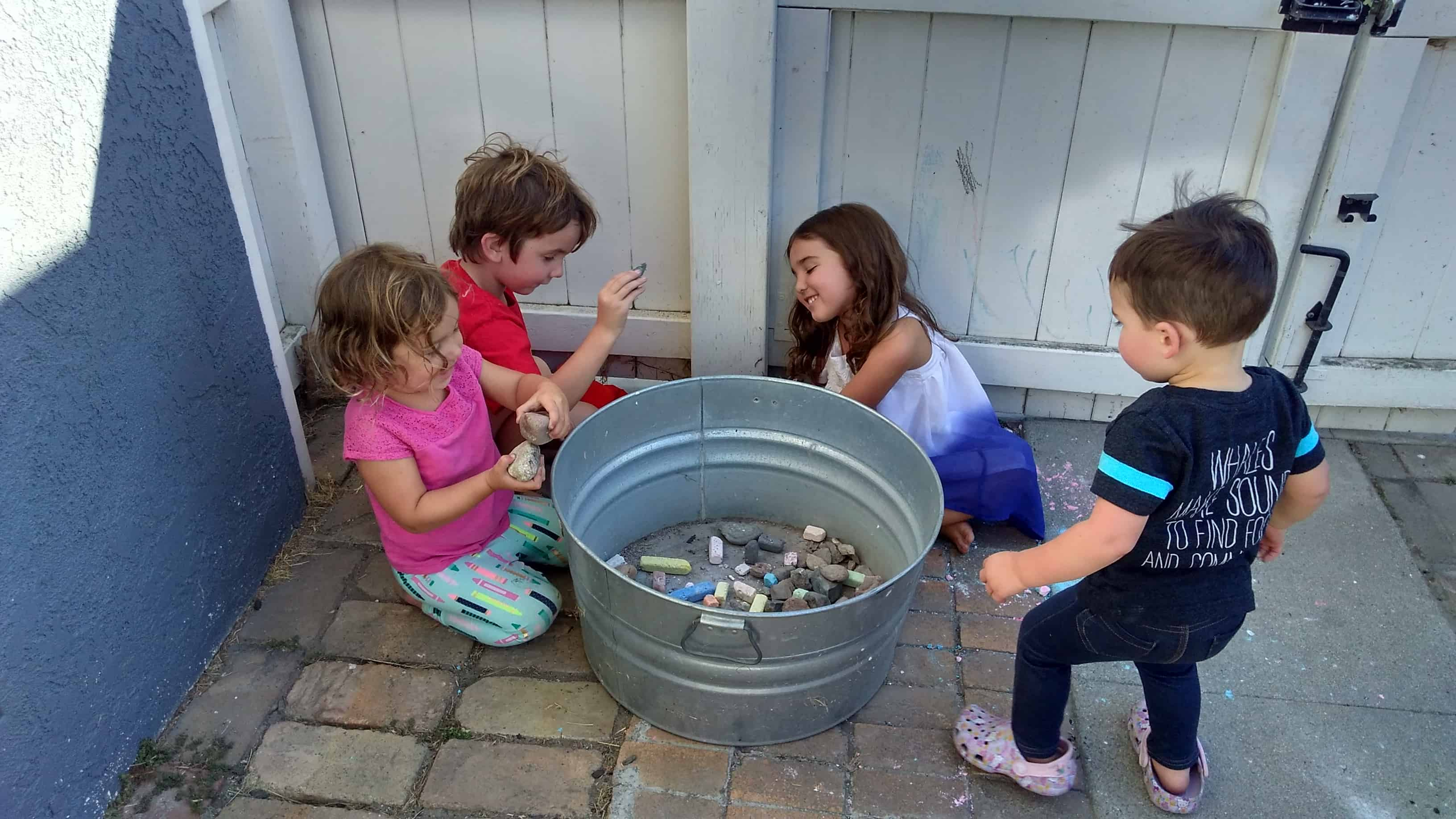Four children placing rocks in a tin barrel