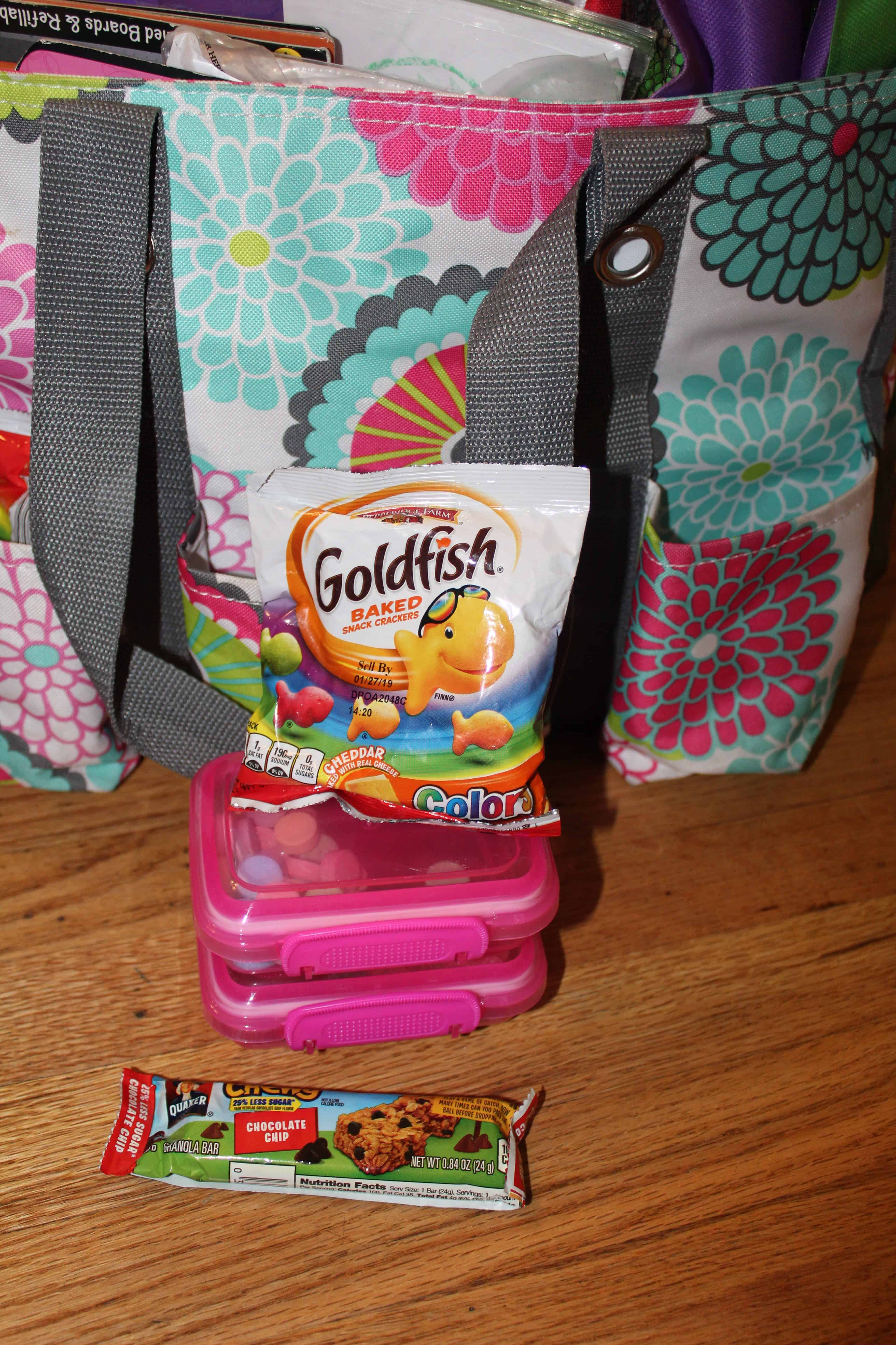 A bag of gold fish, a chewy granola bar and containers of non perishable snacks for the travel activity bag.
