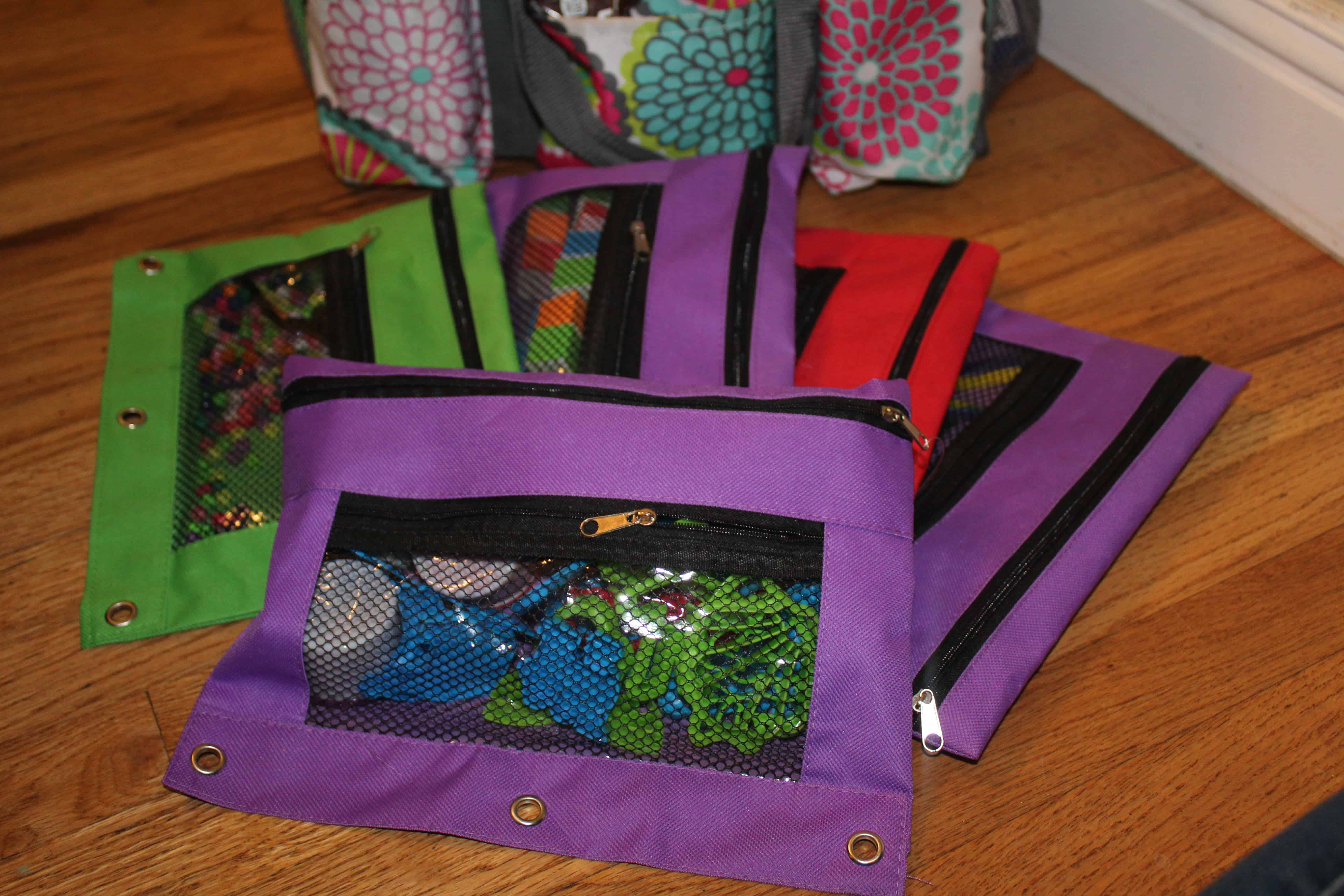 3 ring binder pencil pouches filled with extra toys and items for activities.