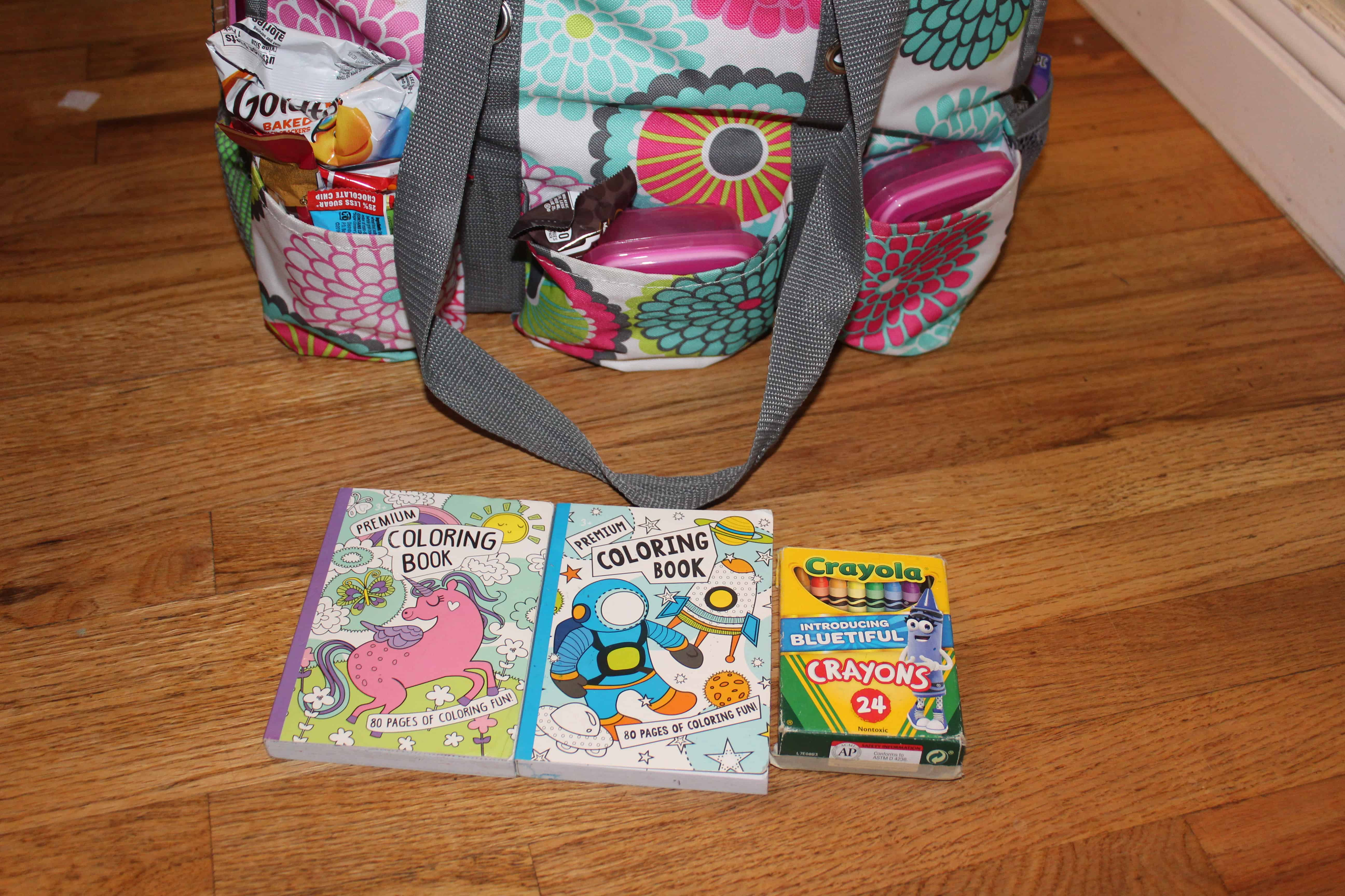 Coloring books and a pack of 24 crayons in front of a travel bag.