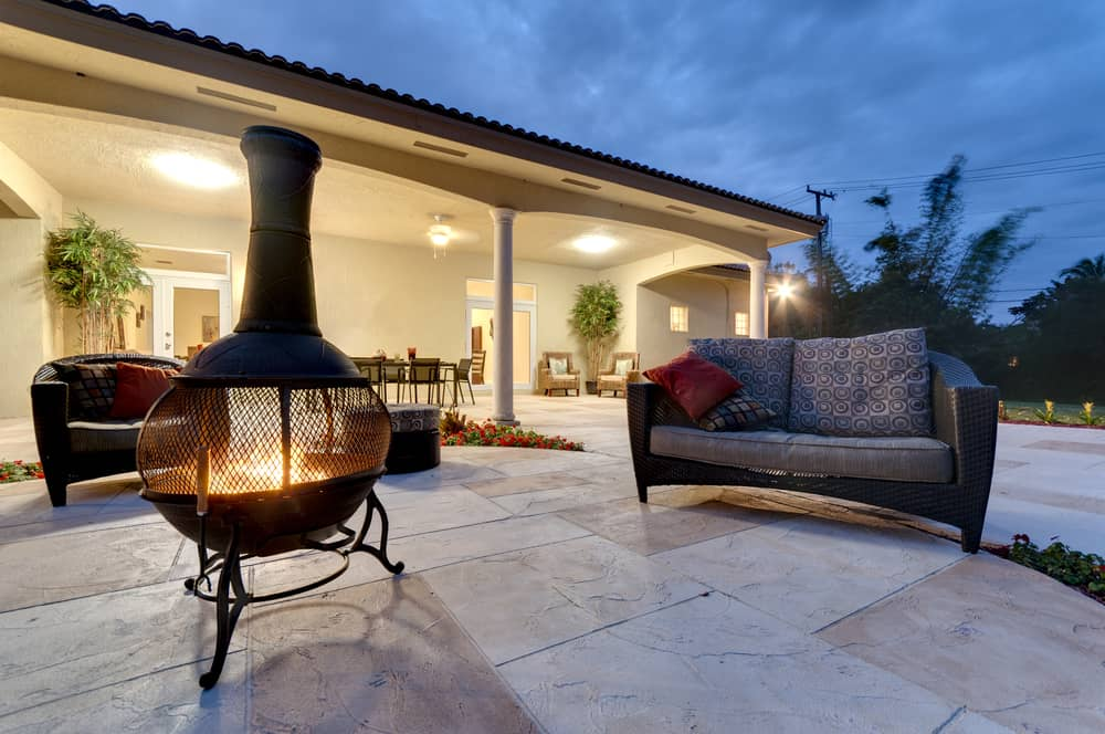 A fire pit lit in a backyard near a couch.