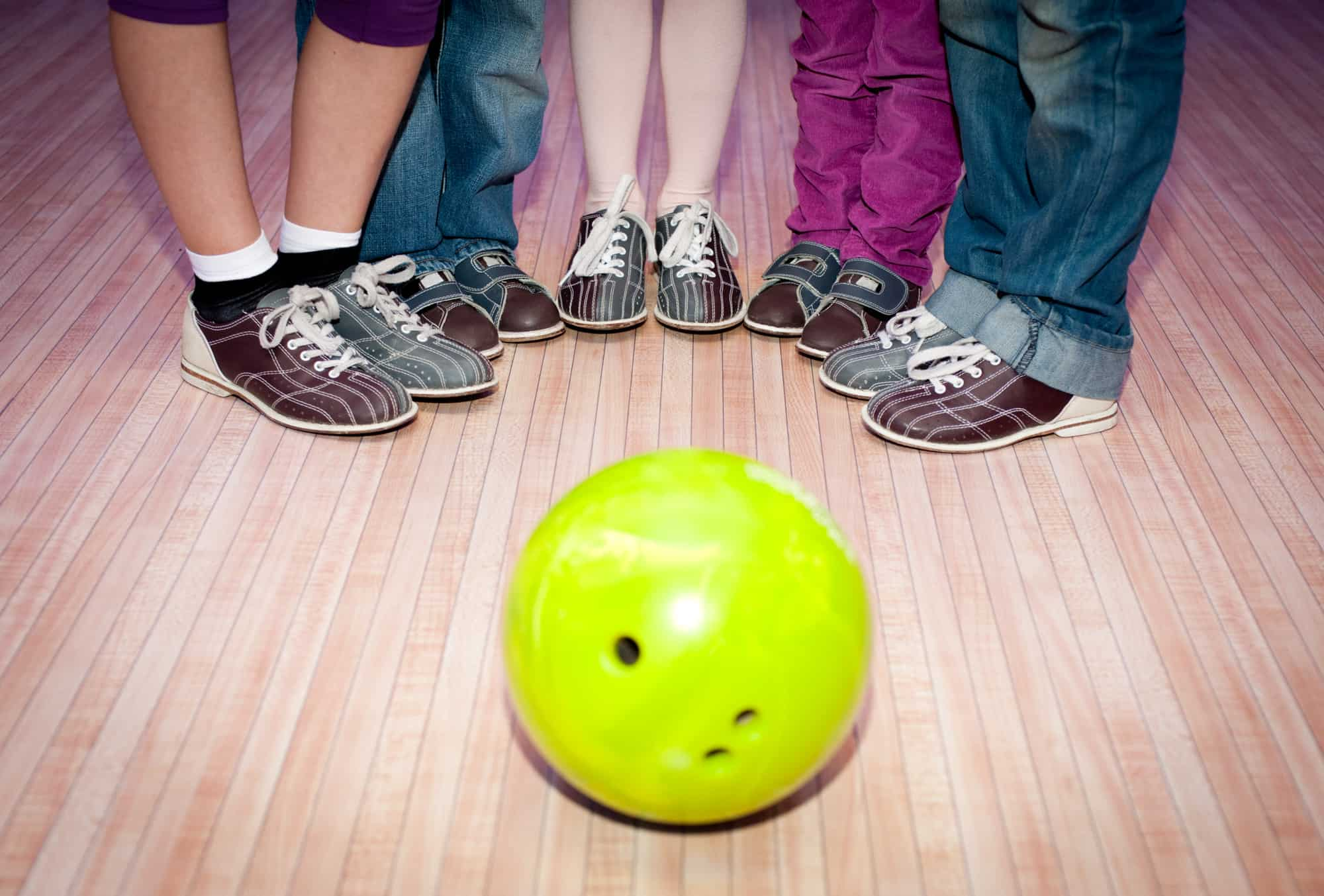 Five different sets of feet representing a family standing around a bowling ball.