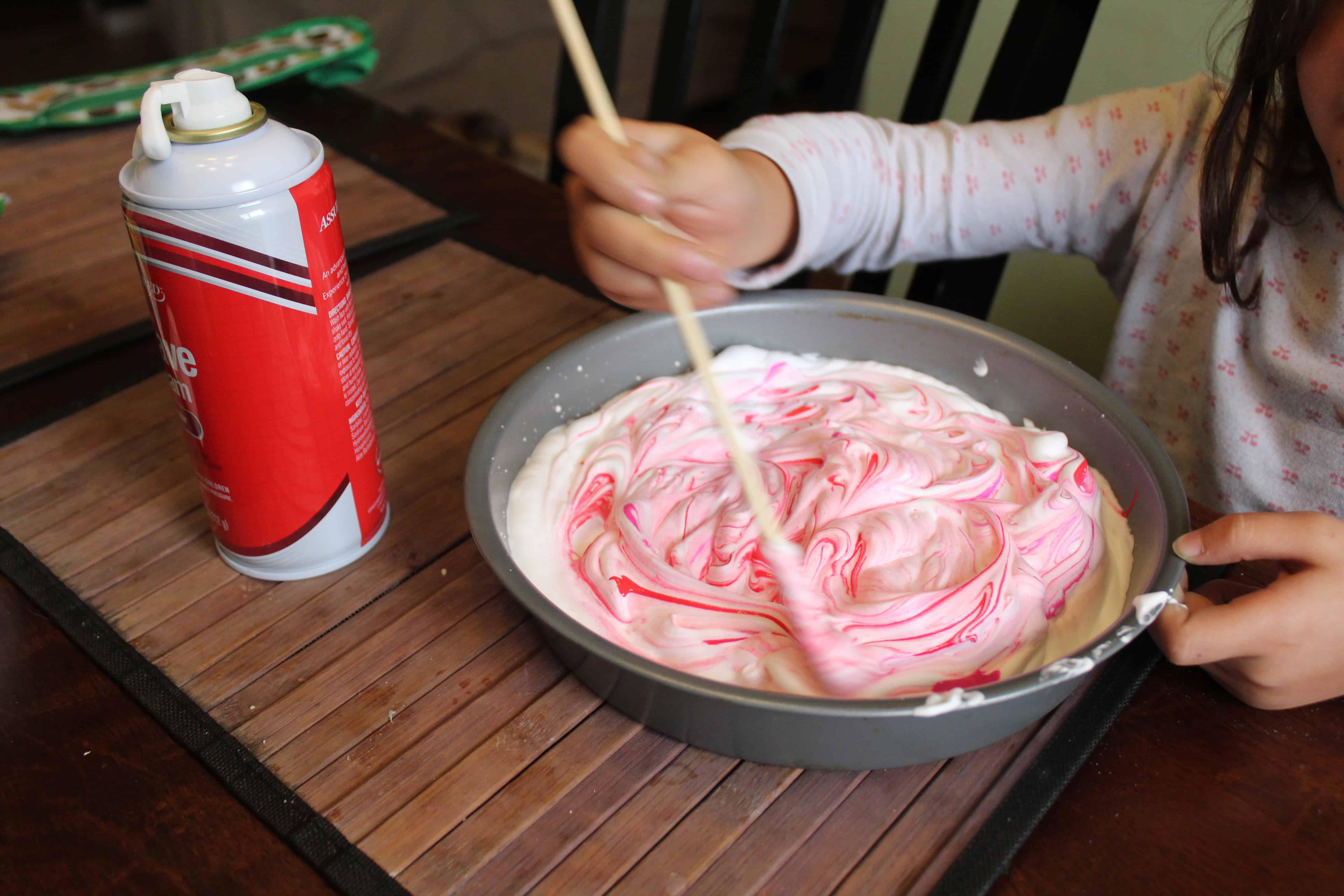 preschooler mixing paint into shaving cream