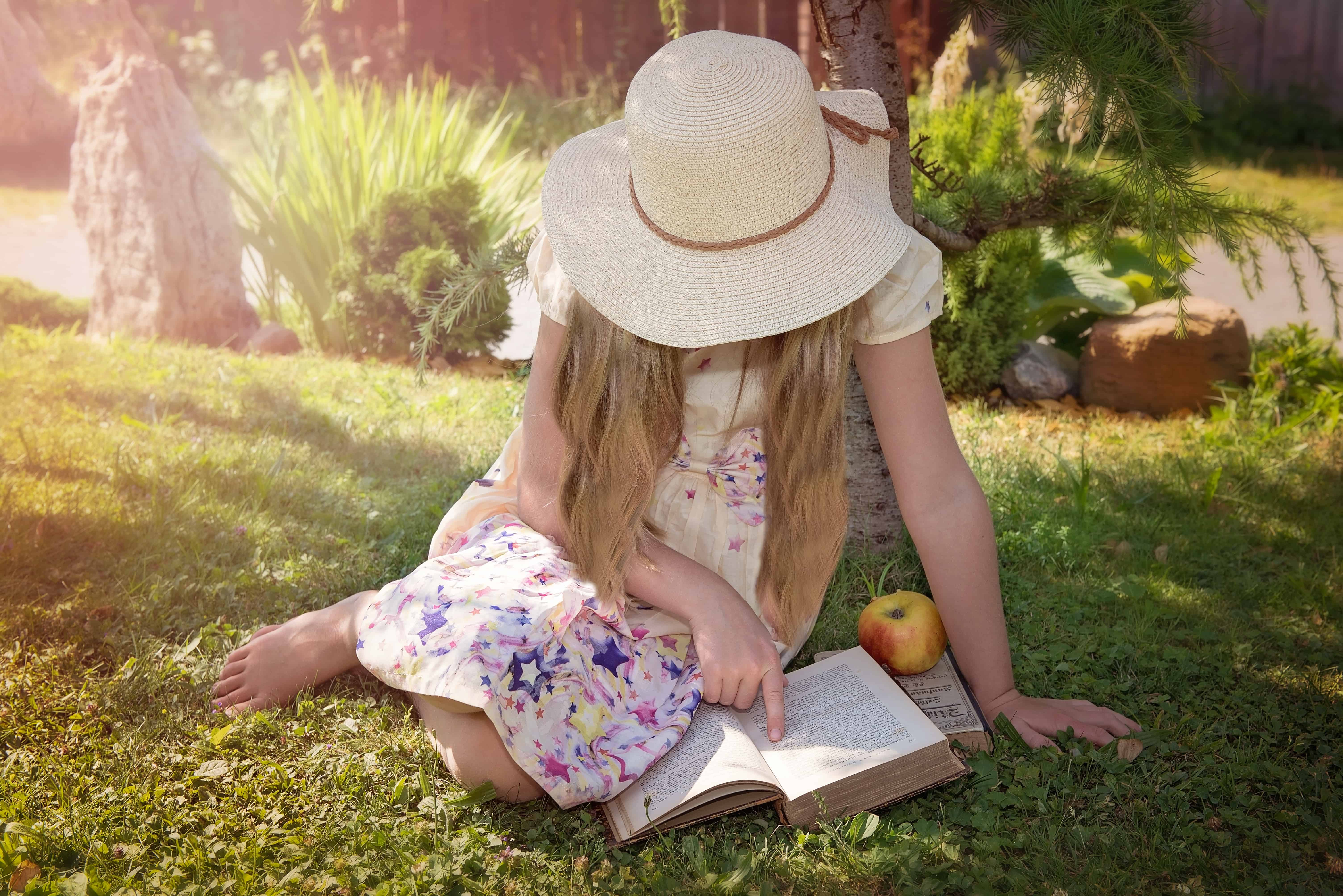 Child sitting in the sun reading a book
