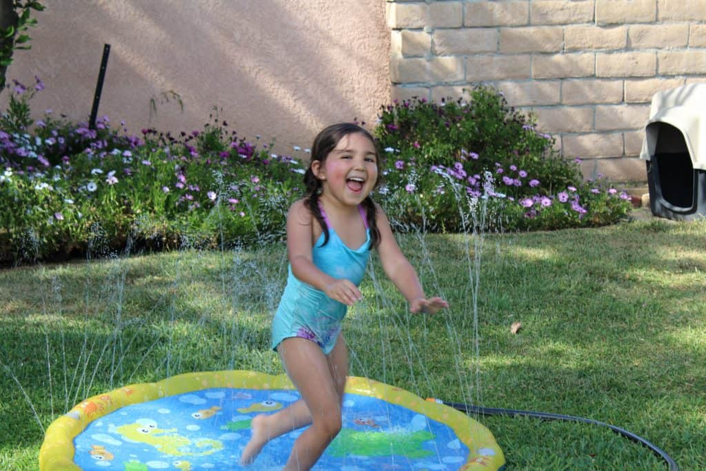 little girl jumping in a sprinkler splash pad