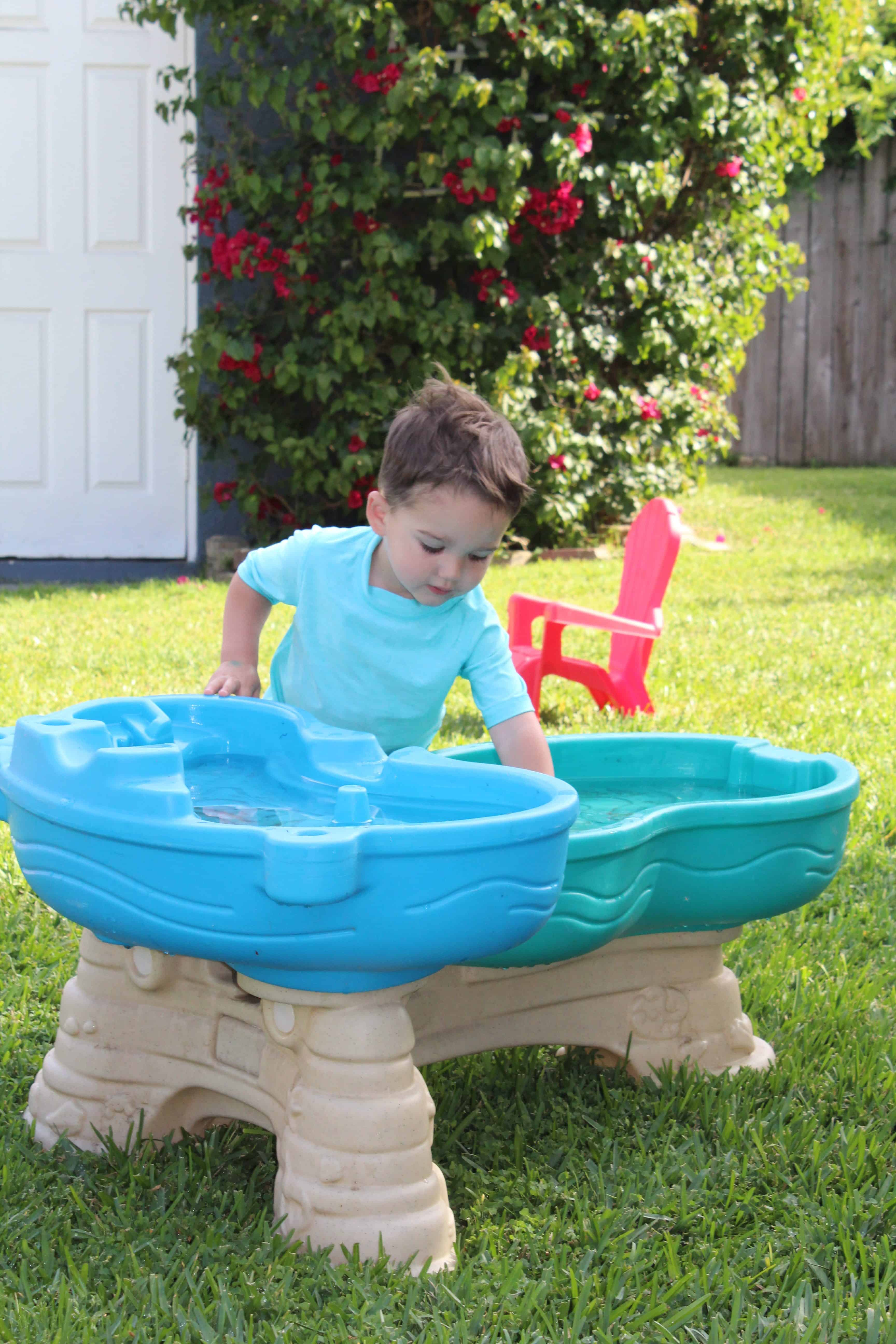 Toddler playing in water table.