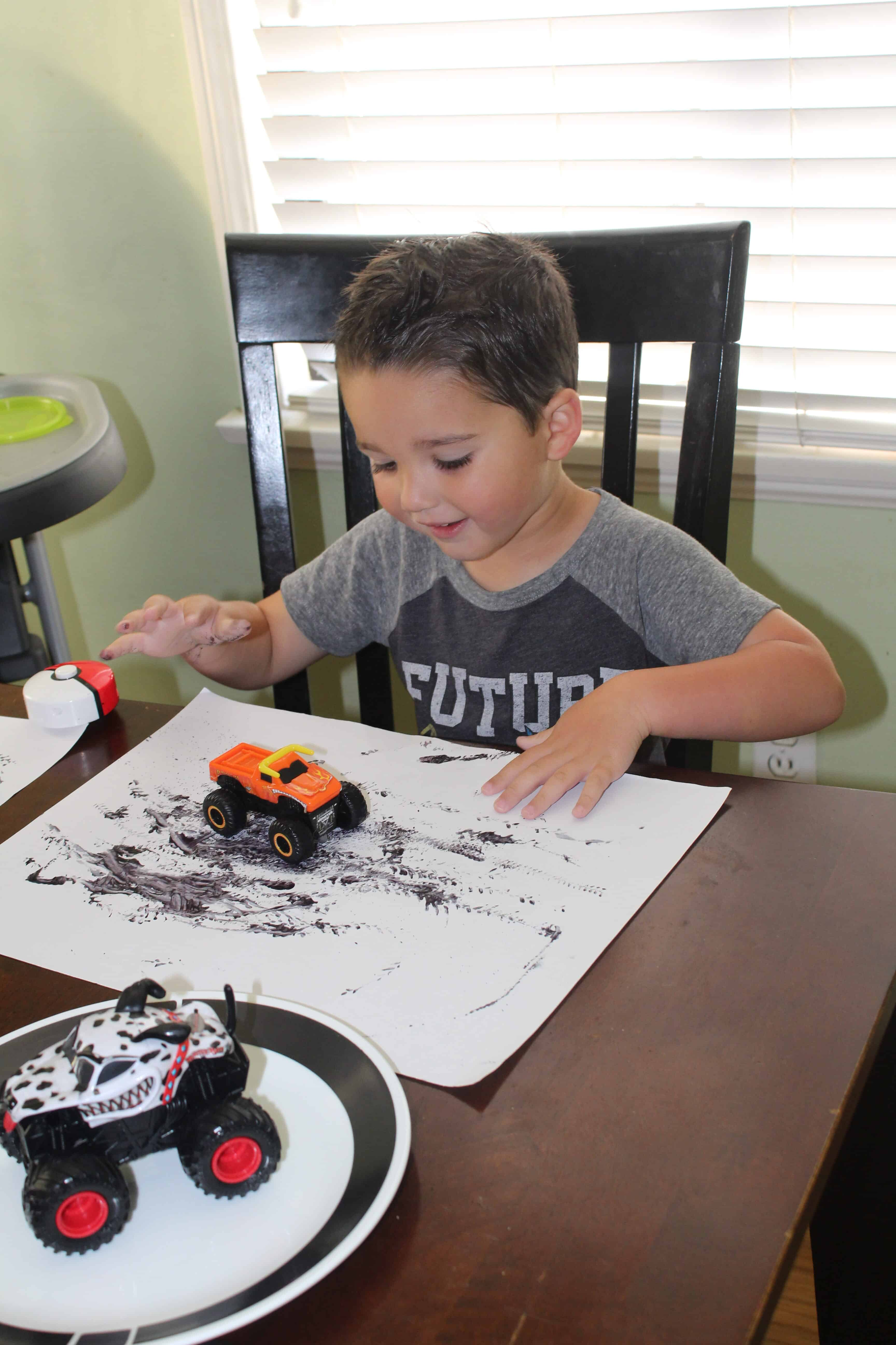 A toddler using a toy car with various patterns on the activity mat