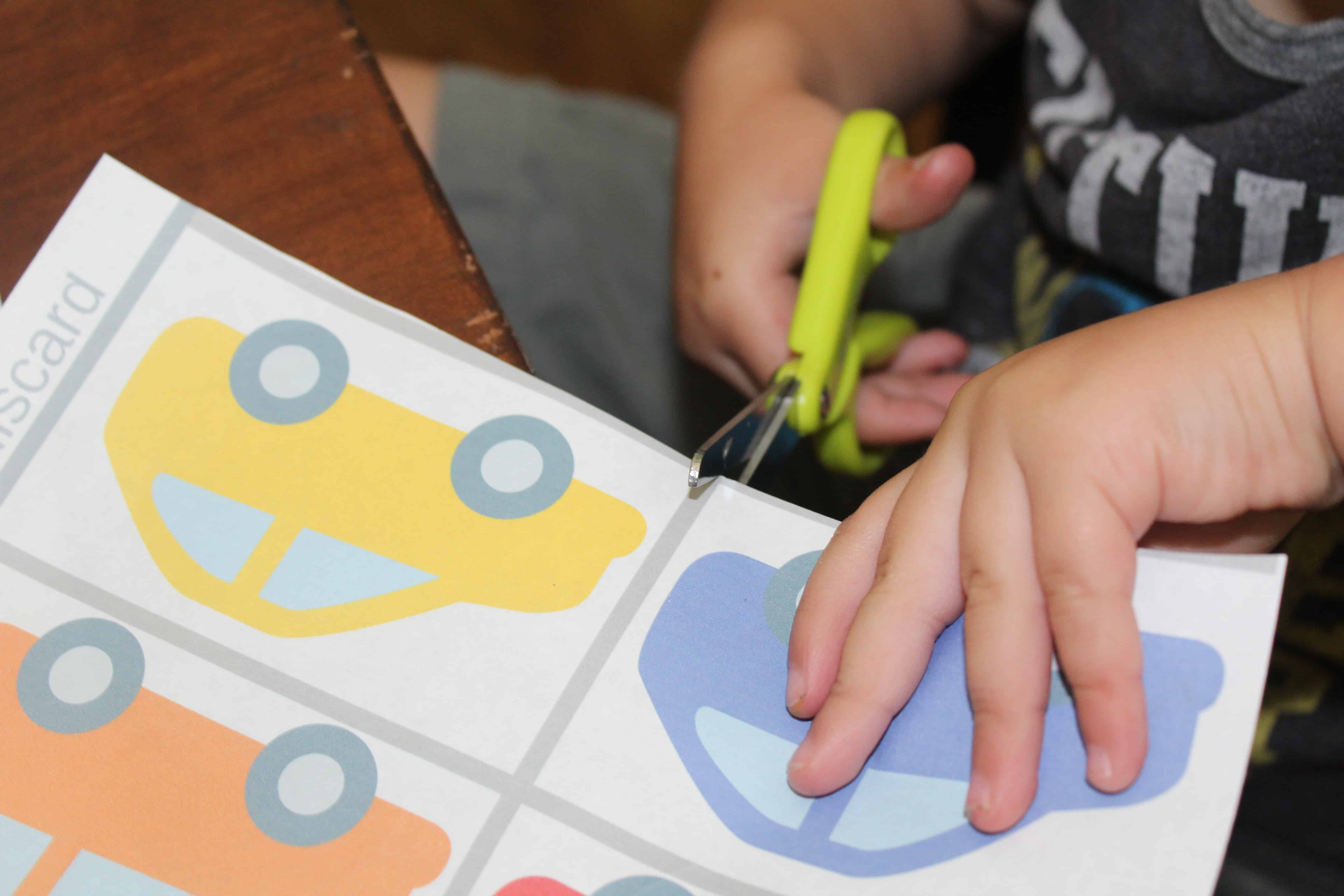 Toddler with safety scissors cutting out car printouts from the activity pack.