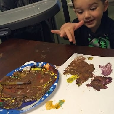 """Toddler with a paper plate full of """"mud paint"""""""