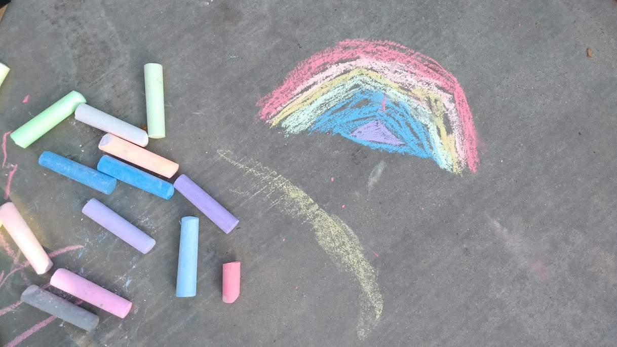 Colored chalk on sidewalk next to a chalk drawn rainbow.