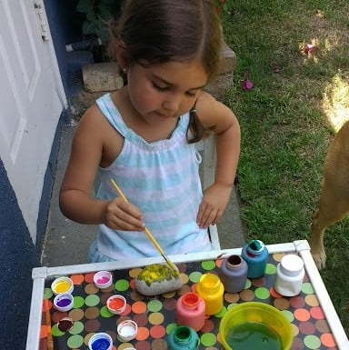 Child using a paint brush and paints to paint a rock.