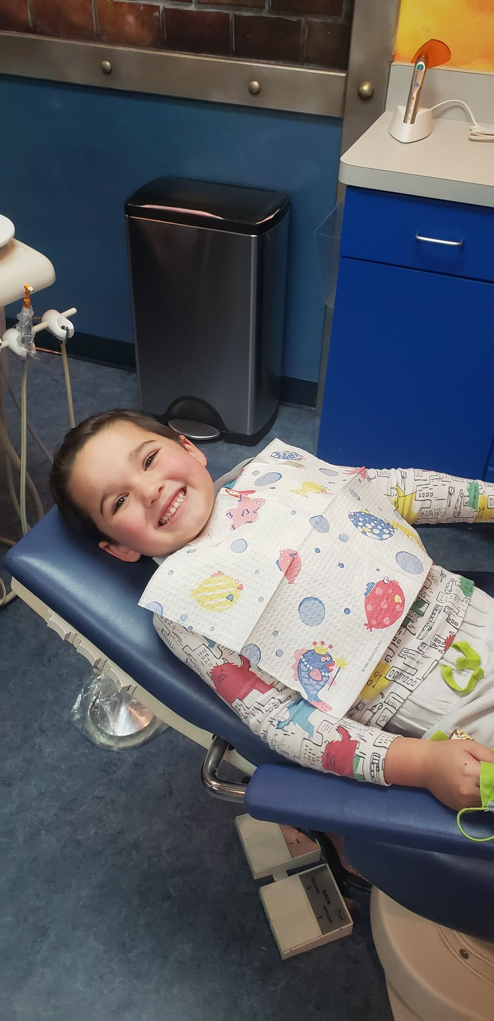 toddler smiling in dentist chair