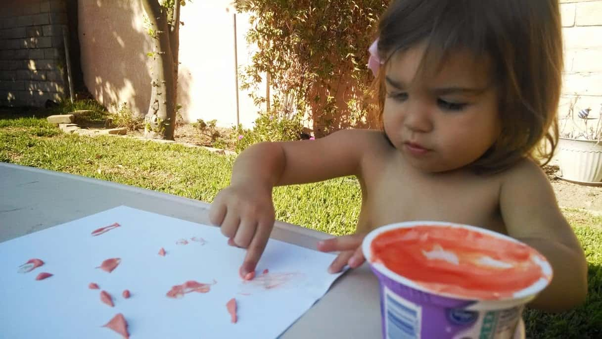 baby using yogurt finger paint