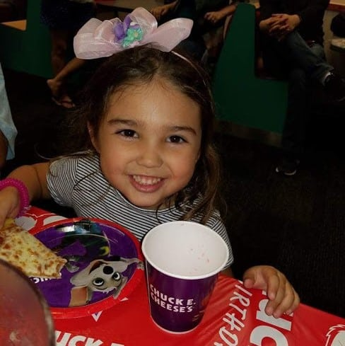 Smiling toddler with Chuck E cheese cup.