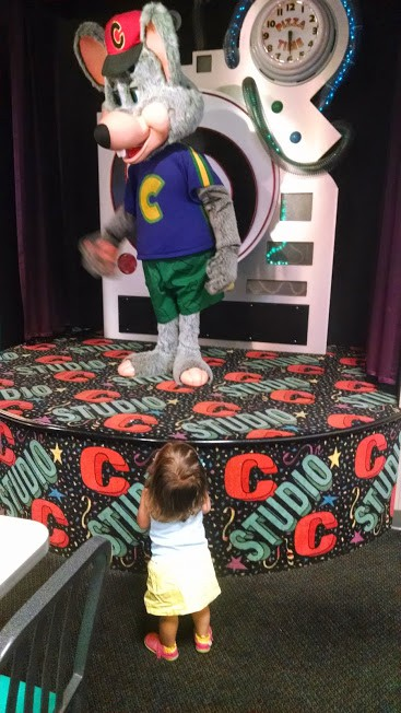 Toddler standing in front Chuck E. Cheese animatronic.