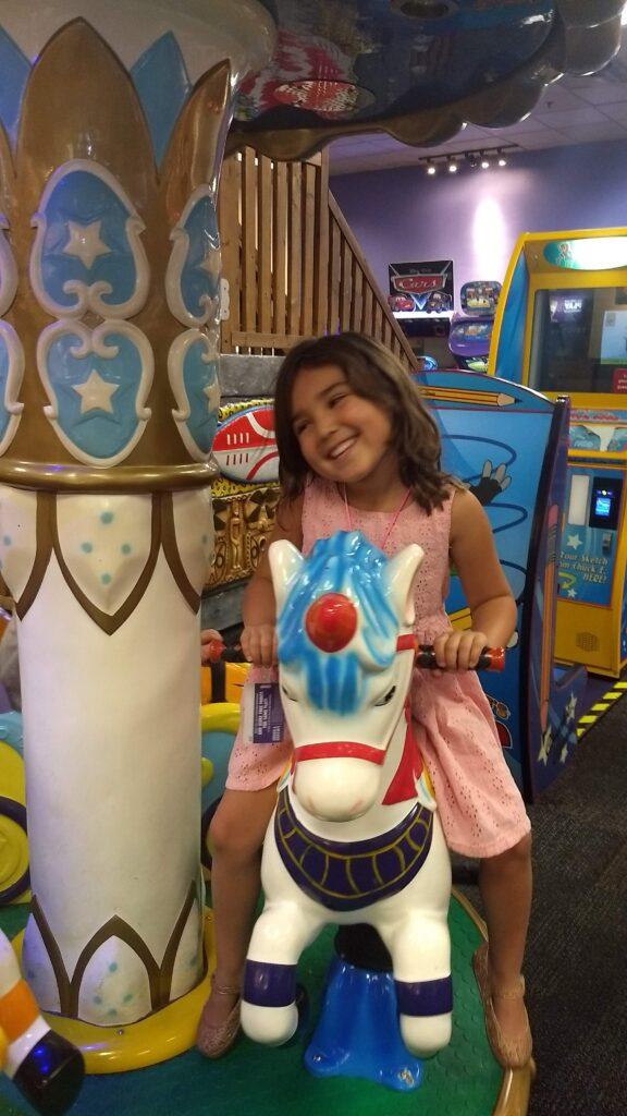 little girl on chuck e cheese ride