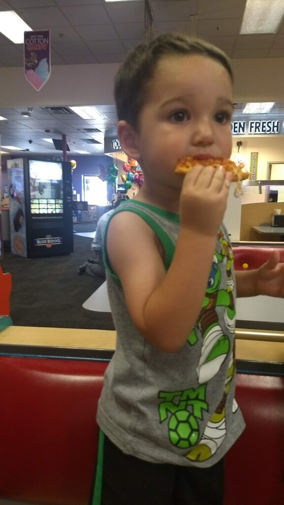 toddler eating pizza at chuck e cheese