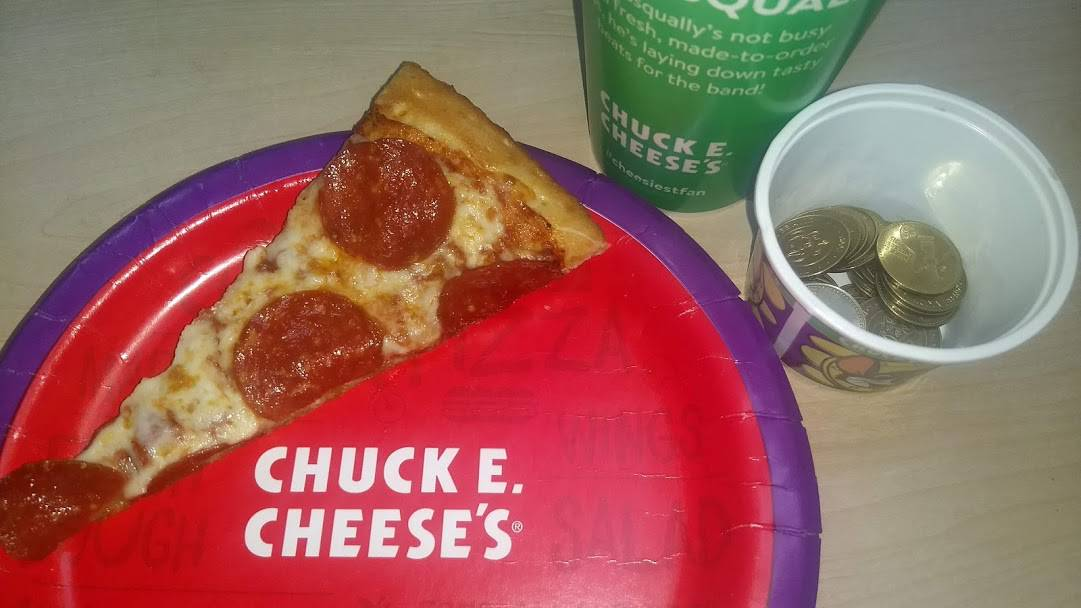 A plate of pizza and a cup of tokens from Chuck E cheese weekday buffet.