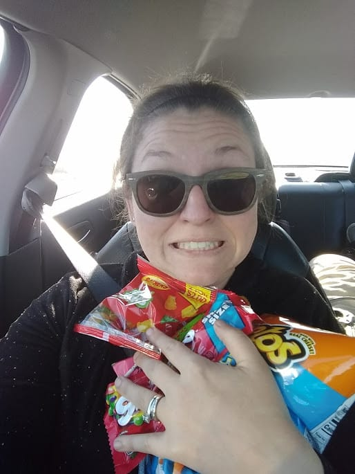Salty mama with loads of snack sitting in the passenger side of a vehicle.
