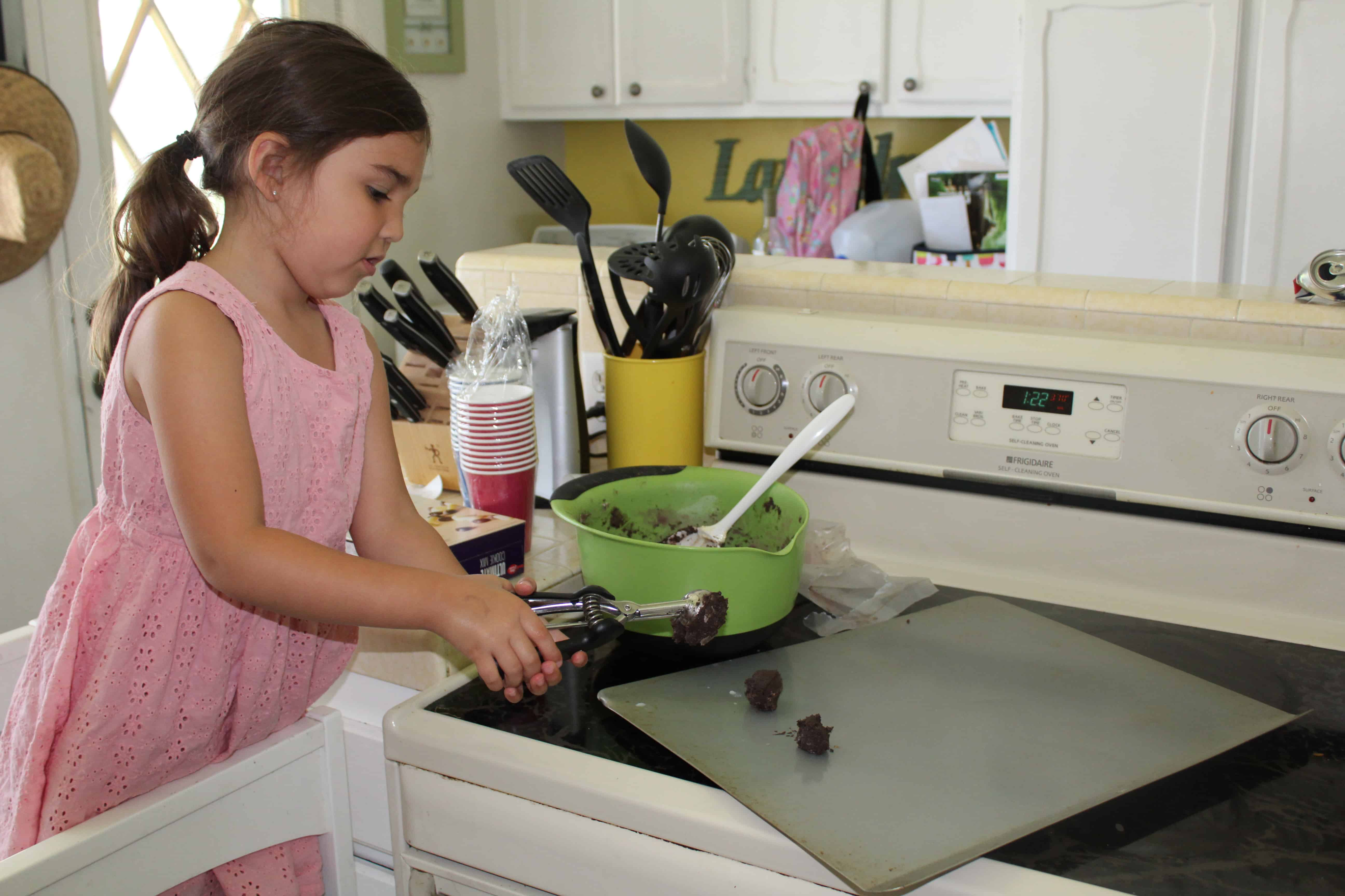 Toddler scooping batter onto a cookie sheet