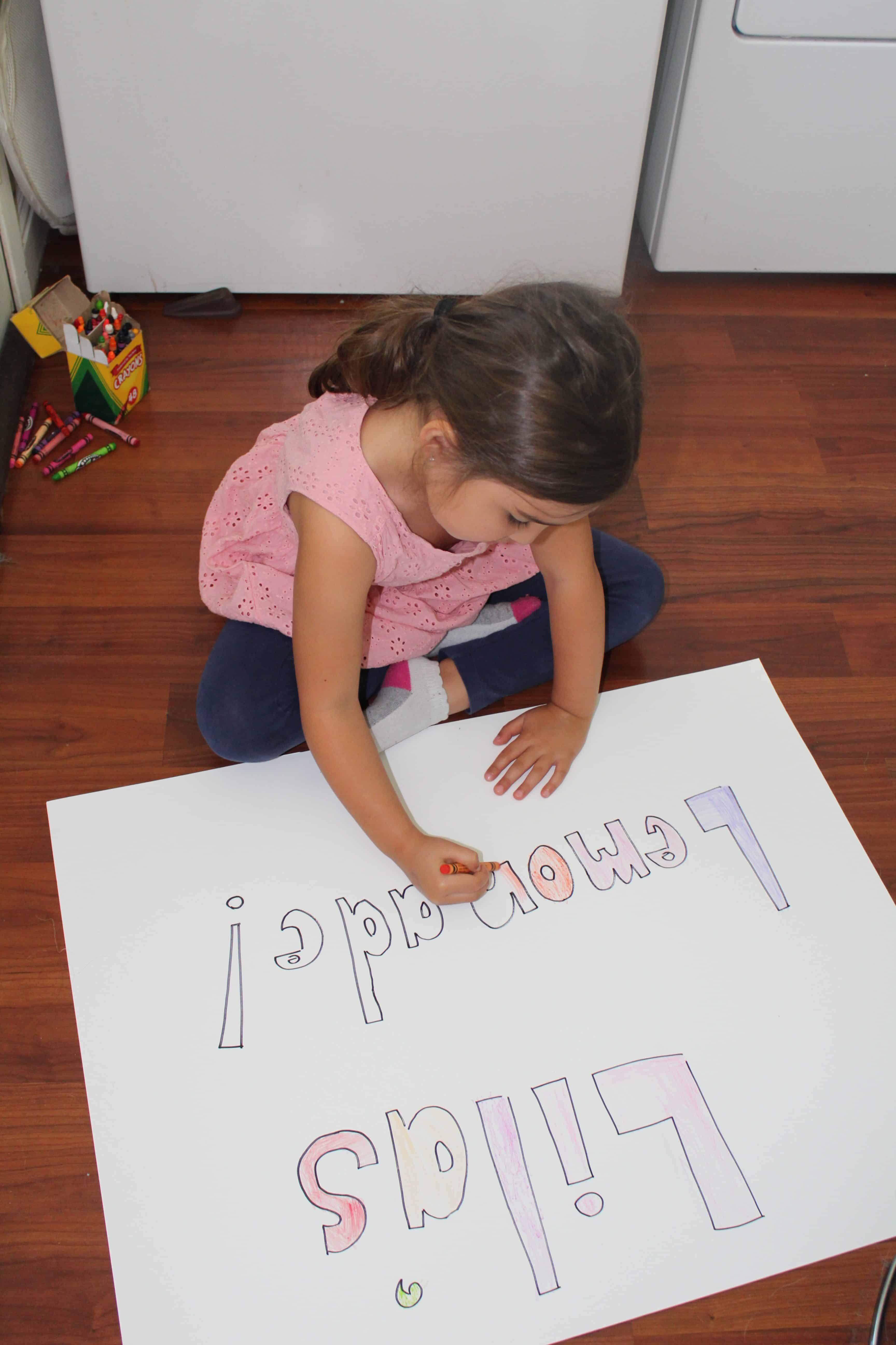 Child coloring lemonade stand sign to advertise