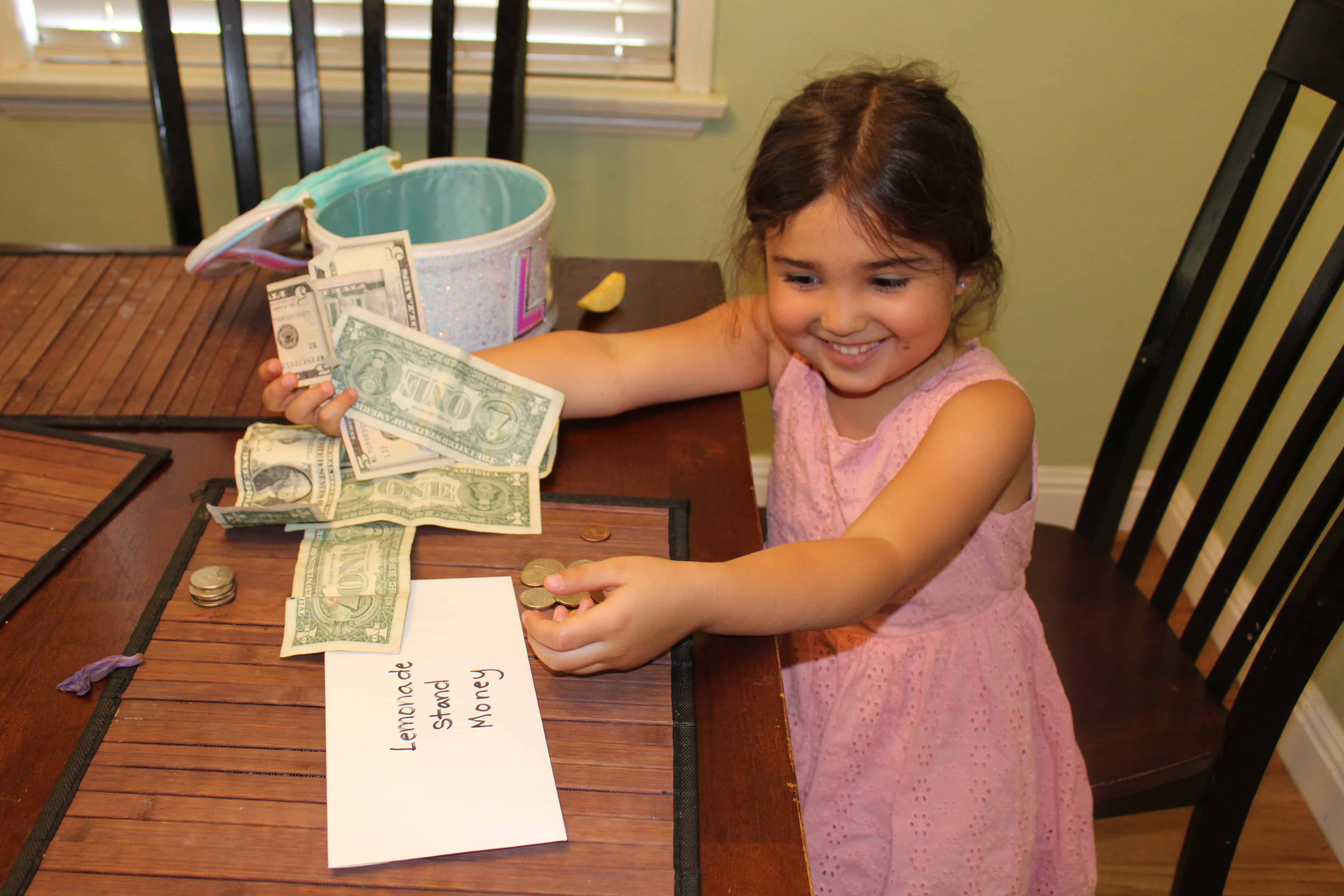 child counting money from her lemonade stand