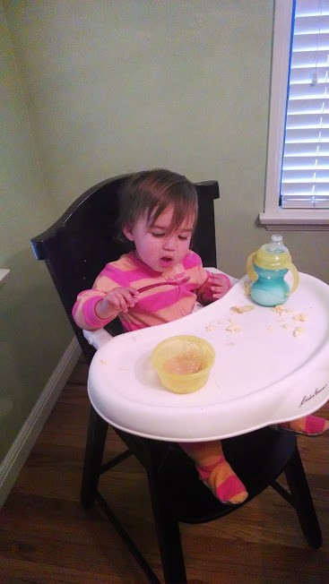 one year old eating applesauce
