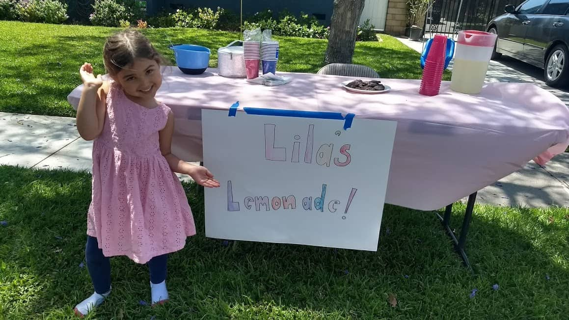 Child standing in front of the table of their lemonade stand smiling.