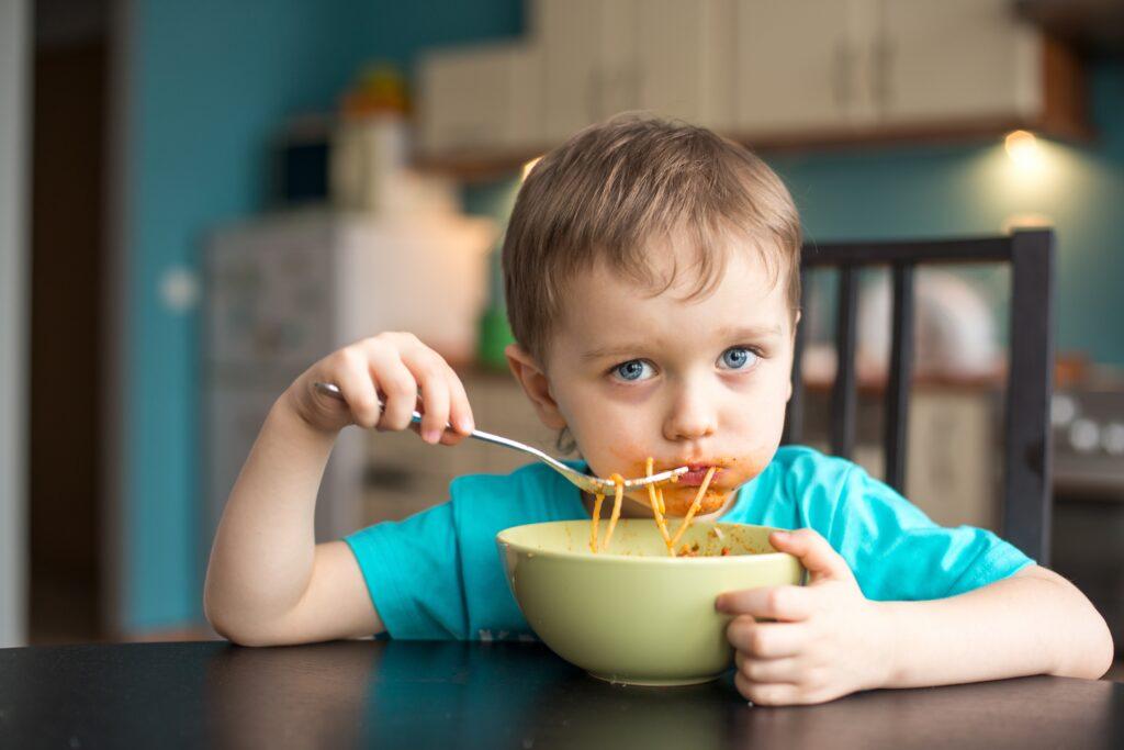 toddler boy eating spaghetti