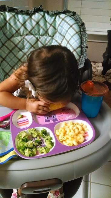toddler eating corn, brocolli, and mac and cheese