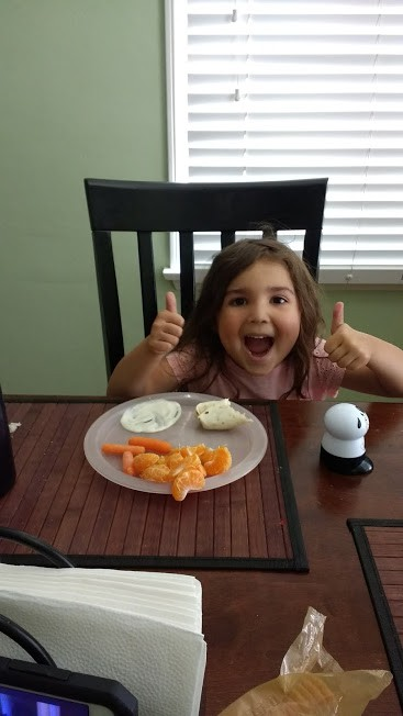 toddler giving fruits and veggies a thumbs up
