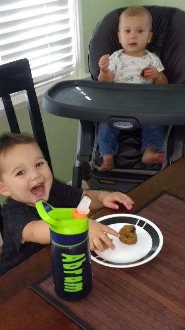 babies eating muffins and smiling