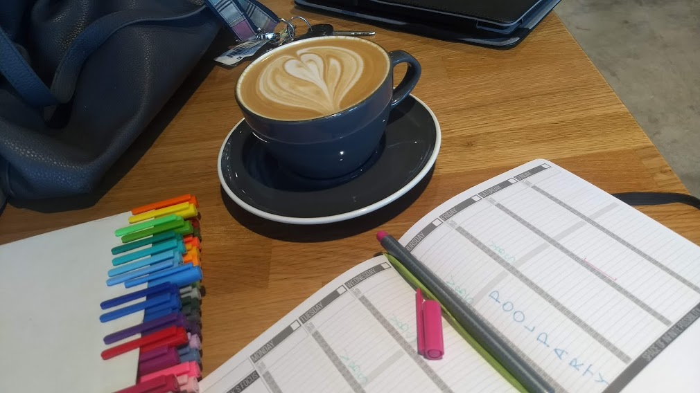 a passion planner, pens, and coffee