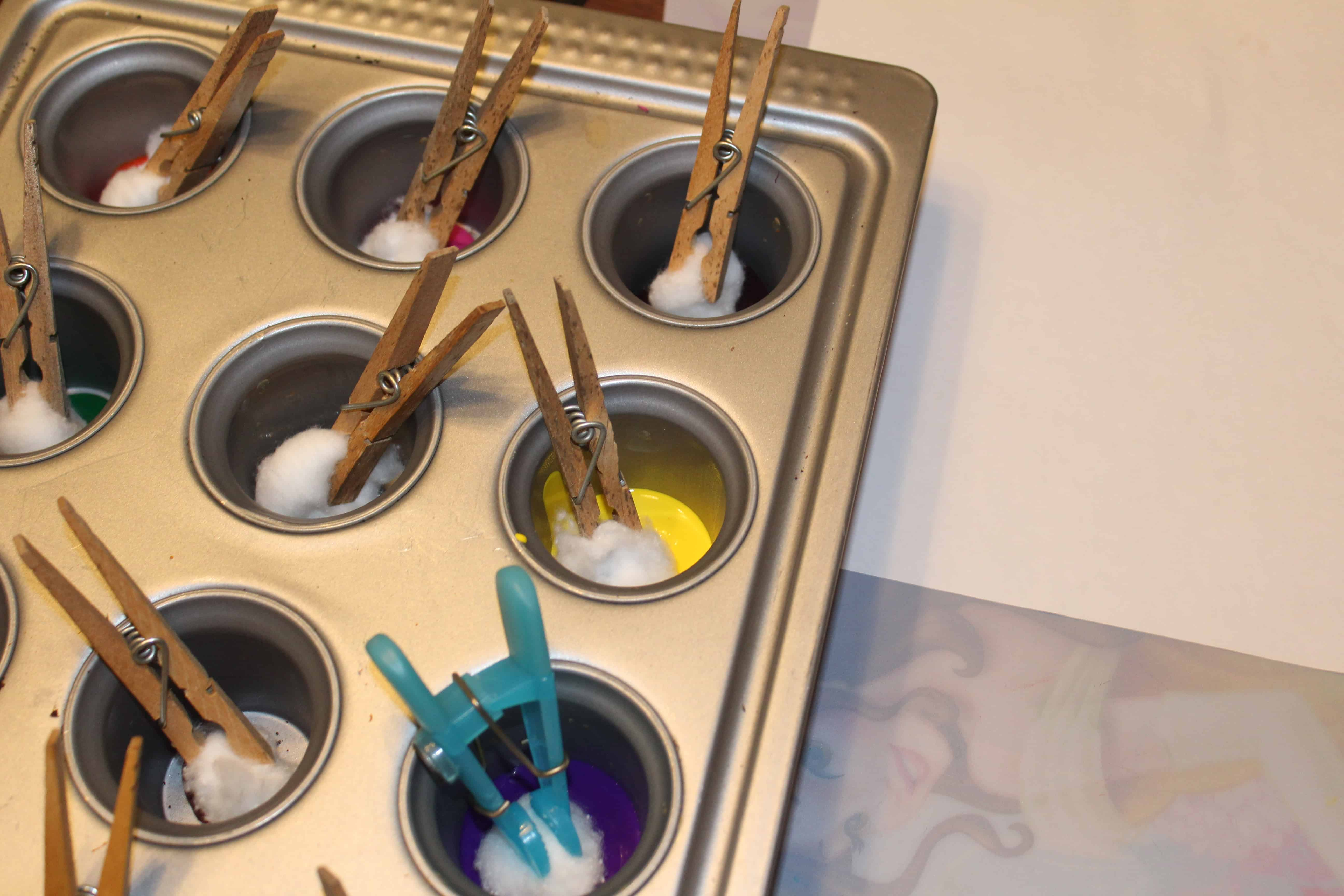 Cupcake tin with different paints in each compartment. Cotton balls held by clothespin dipped in.