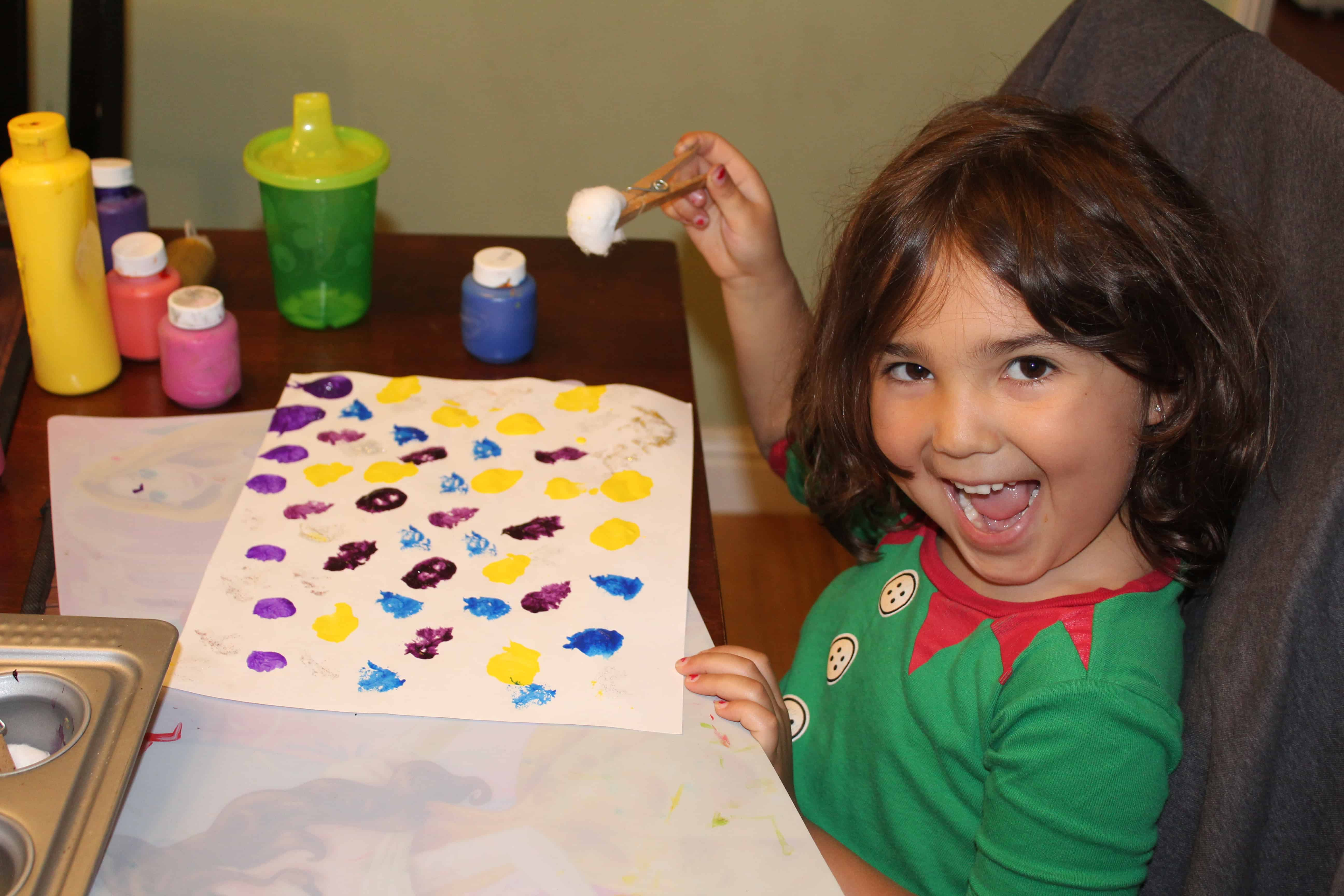 Young girl smiling painting with a clothespin cotton ball on a white sheet of paper