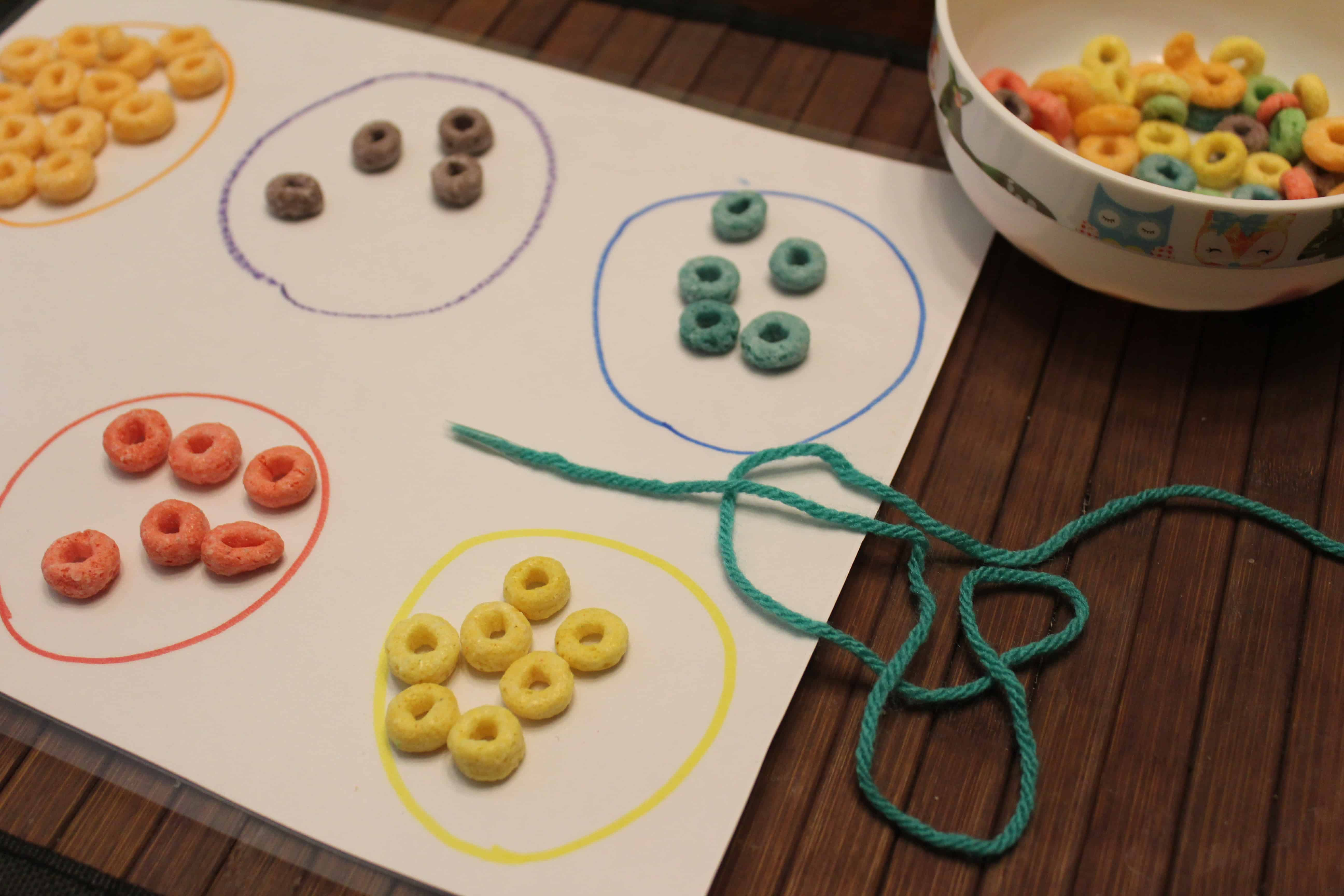 froot loops, sorted by color and about to be put on a string