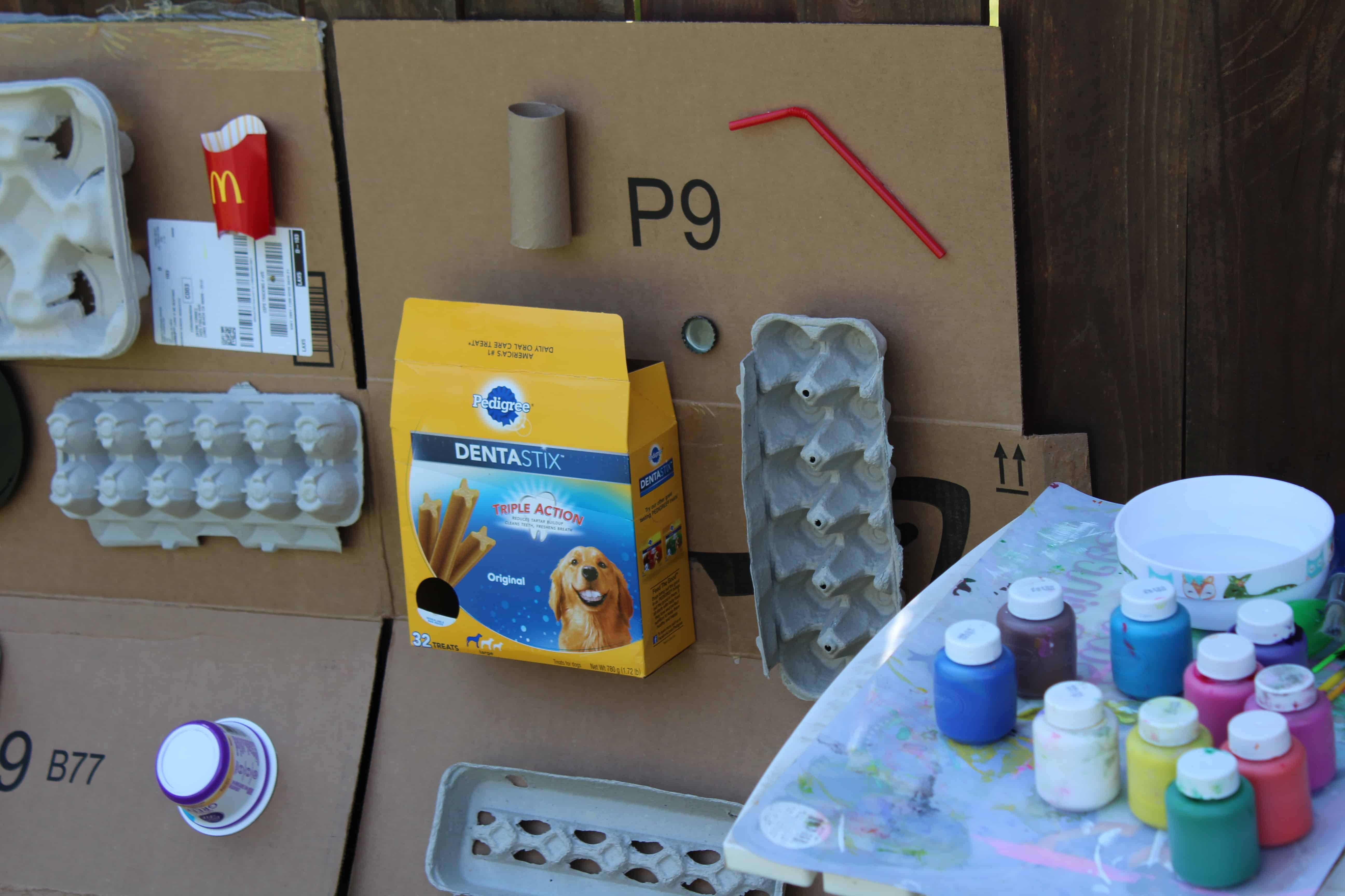 Recycled art materials attached to a flat carboard box. A table of paints for the activities.