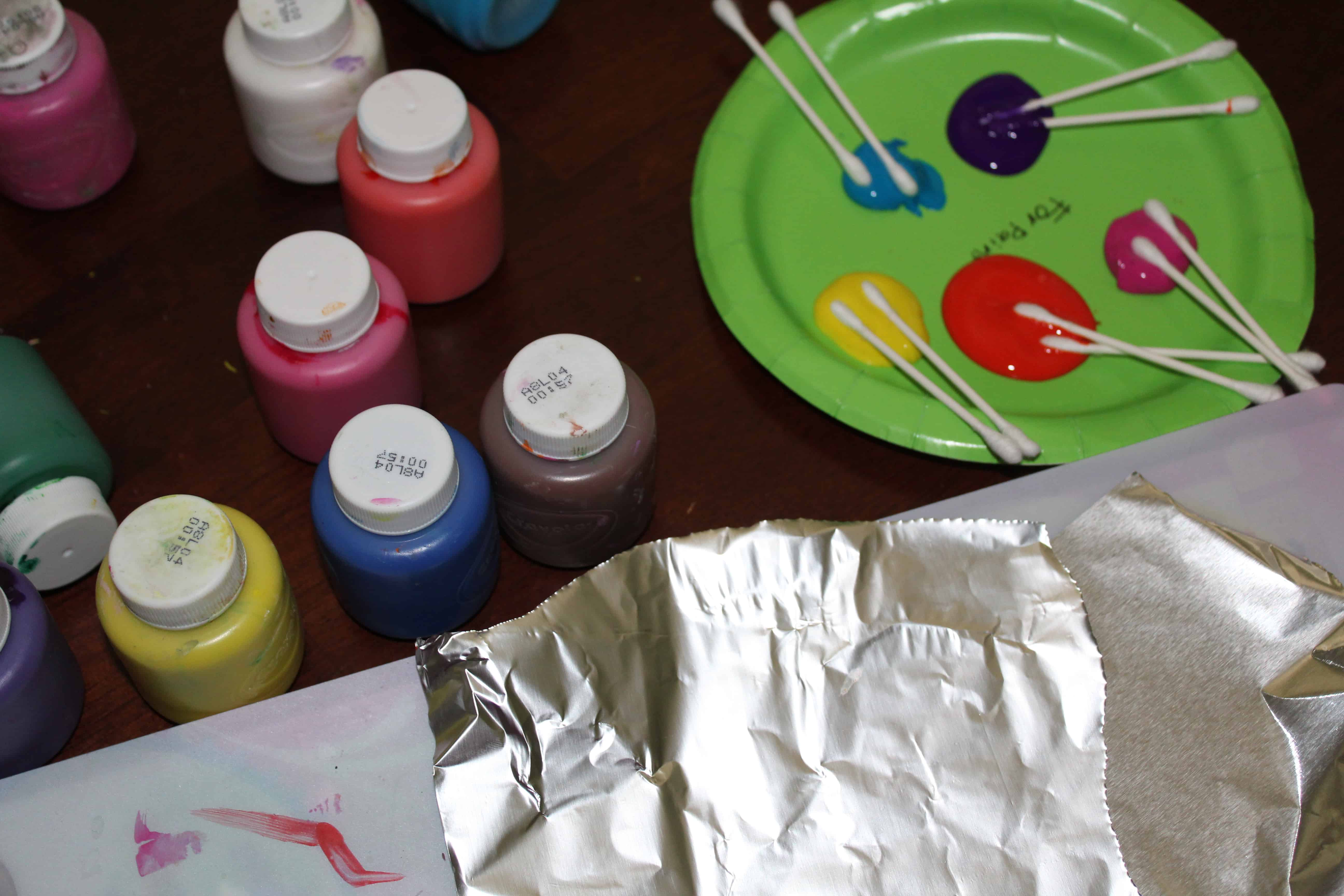 A paper plate with Acrylic paints on it. Containers of paint and a sheet of foil.